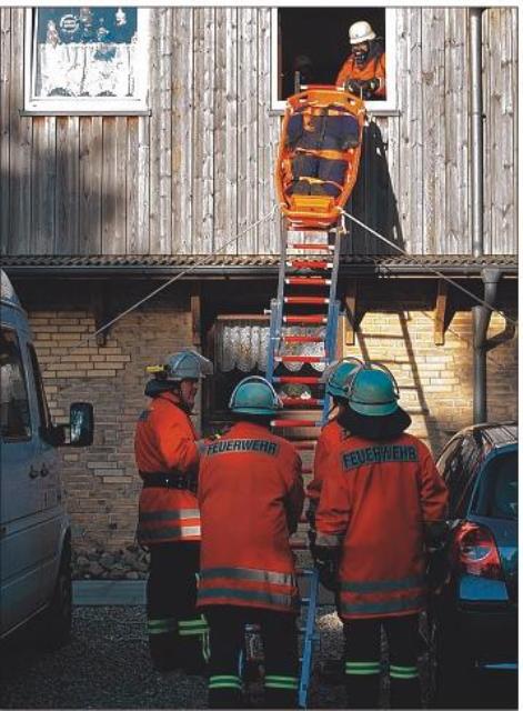 """Mit Hilfe einer Schleifkorbtrage soll ein """"Verletzter"""" durch das Fenster des ersten Stocks gerettet werden."""